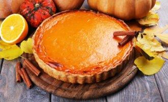 homemade pumpkin pie on cutting board, on wooden background
